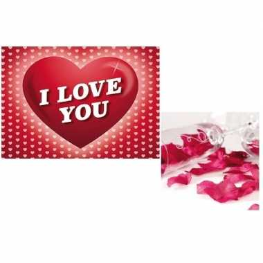 Valentijnsdag cadeau donkerrode rozenblaadjes en valentijnskaart